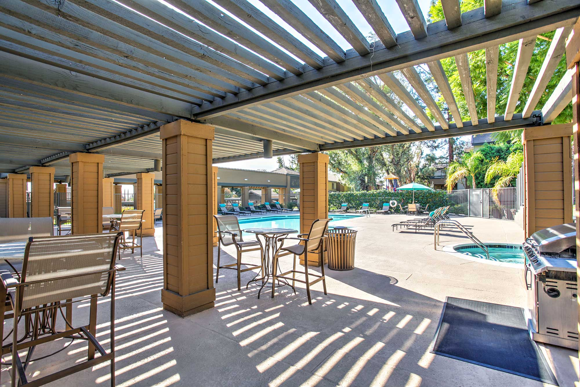 Waterstone Alta Loma Apartments community pool and lounge area with barbecue